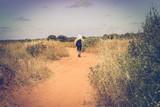 Einsame Frau auf einem Sandweg in der Hitze von Spanien - 230696211