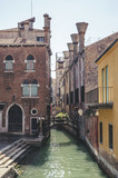 Traditional narrow canal with gondolas in Venice, Italy - 230696886