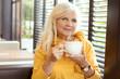 Beautiful senior woman drinking cofee.