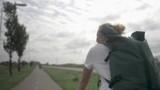 Beautiful young blonde woman with backpack riding a bike on bike path in Myrte-boerderijen. Netherlands. Blur effect - 230736012