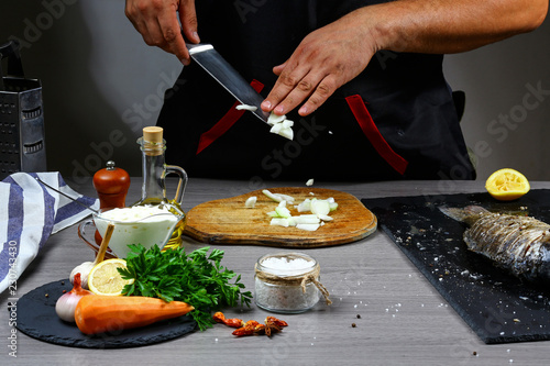 Wall mural Knife cutting onion. Sliced vegetables on wooden board. Ingredient for Stuffed Fish with Vegetables