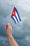 Hand holding Cuba flag high in the air, with a stormy, cloudy sky