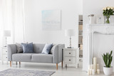 Lamp on white cabinet next to grey couch in simple flat interior with plants and candles. Real photo - 230759067