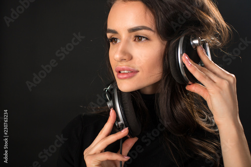 Close-up portrait of young beautiful brunette woman listening to music and holding headphones over dark grey background. - 230763234