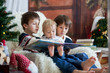 Leinwandbild Motiv Three children, boy brothers, sitting in rocking chair in cozy living room with christmas decoration, reading a book