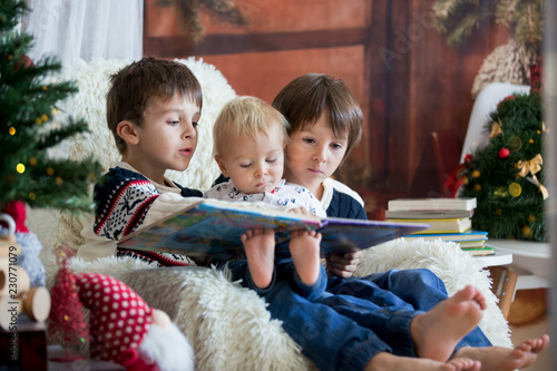 Leinwanddruck Bild Three children, boy brothers, sitting in rocking chair in cozy living room with christmas decoration, reading a book