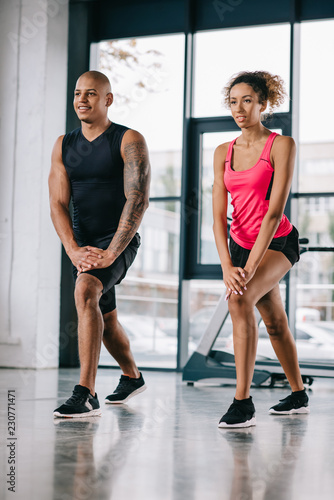 Sticker smiling african american couple of athletes doing exercise at gym