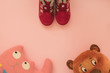 Burgundy women's winter boots for children on a pink background with children's toys, copyspace, flatlay