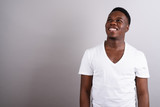 Portrait of young African man against white background - 230776417