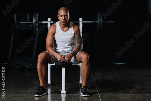 serious african american male athlete looking at camera and sitting at gym - 230778237