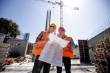 Structural engineer and construction manager in orange work vests and hardhelmets discuss documentation and talk by phone on the open air building site - 230781874