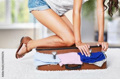Leinwandbild Motiv Young  woman wearing shorts sitting on suitcase