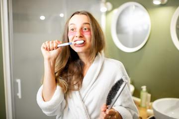 Young and beautiful woman in bathrobe brushing her teeth in the bathroom © rh2010