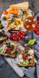 Appetizing toasts with avocado, quail eggs, tomatoes, Dor Blue cheese and a glass of cold white wine. Author's cuisine. Original serving dishes - 230806421