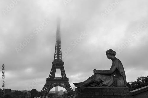 Eiffel Tower, famous landmark, with a female sculpture on the forefront.