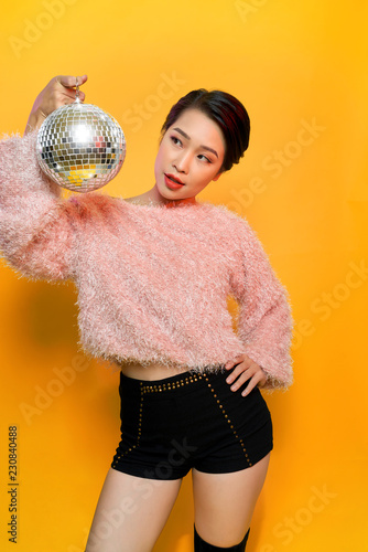 Portrait of charming young female showing tongue and fooling around holding mirror ball on head posing on yellow background. Party and glitter fashion concept - 230840488