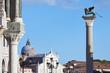 San Marco winged Lion statue on column and San Giorgio Maggiore basilica, blue sky in Italy