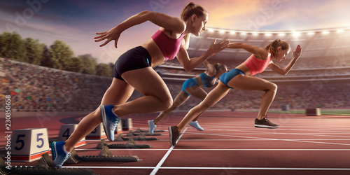 Female athletes sprinting. Three women in sport clothes run at the running track in professional stadium
