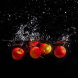 Cherries in water splash. Isolated on black background