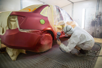 Repair and painting car car mechanic. Auto mechanic worker painting car in a paint chamber during repair work. Auto repairman plastering autobody bonnet.