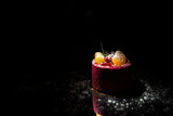 Tasty red cake with fruit on a black background
