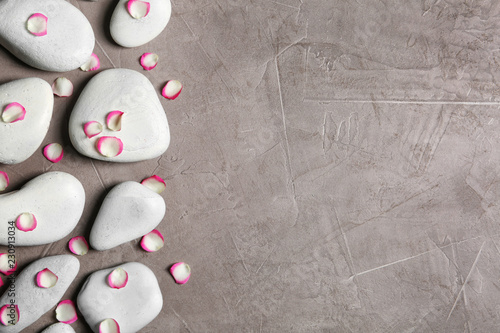 Leinwanddruck Bild Flat lay composition with spa stones and flower petals on grey background. Space for text