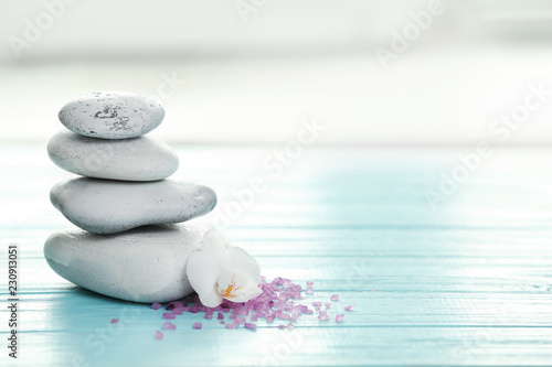 Leinwanddruck Bild Spa stones, sea salt and flower on table against blurred background. Space for text
