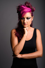 Beautiful woman with pink hair and make-up against gray backgrou © Ranta Images