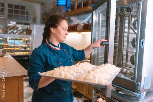 Rogaliki w piekarniku. Doświadczony francuski piekarz ubrany w niebieską kurtkę czuje się zajęty wprowadzanie rogaliki w piekarniku