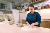 Many orders. Dark-haired female baker feeling pressed for time having too many orders in the morning - 230928412