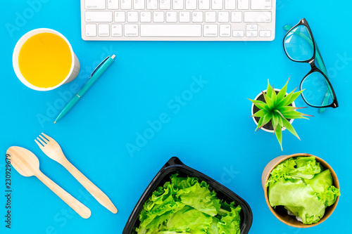 Order healthy food delivery to office. Light, diet meal with lettuce in plastic containers near computer keayboard and glasses on blue background top view
