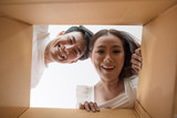 Happy couple opening a box and looking inside to product - 230935683