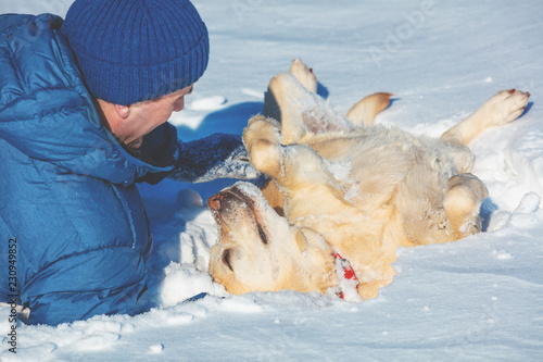 Leinwanddruck Bild A happy man with a Labrador retriever dog lying on the snow in winter. The dog lying on back