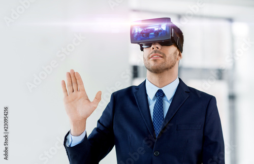 Foto Murales business, technology, augmented and virtual reality concept - businessman with some machine on display of vr headset at office