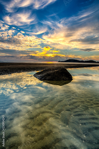 Beautiful A long exposure picture of sunrise over a sand beach - 230954243
