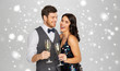 christmas party, new year celebration and holidays concept - happy couple with glasses drinking non alcoholic champagne over grey background and snow