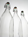 close -up of 3 empty transparent glass bottles of 1 liter with orange and green cap - 230962052