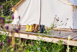 Close-up of a canvas bell tent with shoes on a wooden base - 230962638