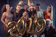 New 2019 Year is coming! Group of cheerful young multiethnic people in Santa hats carrying gold colored numbers and throwing confetti on the party - 230966271