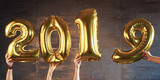 New 2017 Year is coming! Golden balloons with numbers in the hands on dark background - 230966249