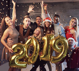 New 2019 Year is coming! Group of cheerful young multiethnic people in Santa hats carrying gold colored numbers and throwing confetti on the party - 230966264