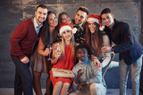 New Year is coming! Group of cheerful young multiethnic people in Santa hats on the party, posing emotional lifestyle people concept - 230966289