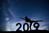 Silhouette young girl is relaxing. 2019 new year background of the Milky Way galaxy on a bright star dark sky tone - 230966417