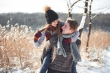 Happy couple playful together during winter holidays vacation outside in snow park - 230966605