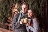 Photo of happy man and pretty woman with cups outdoor in winter. Winter holiday and vacation. Christmas couple of happy man and woman drink hot wine. Couple in love - 230966694