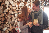 Young couple having breakfast in a romantic cabin outdoors in winter. Winter holiday and vacation. Christmas couple of happy man and woman drink hot wine. Couple in love - 230966809