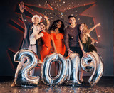 The new 2019 is approaching. A group of merry young multinational people in Santa's hat with silver numbers and throwing confetti at the party. Happy New Year. - 230967221