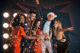 A group of friends are having fun in beautiful chiffon dresses with champagne and confetti, preparing for the New Year - 230967495