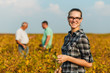 Group of farmers standing in a field examining soybean crop before harvesting. Young female farmer looking at camera.
