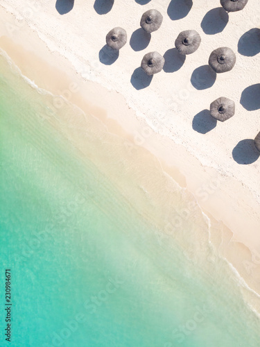 Foto Murales Aerial view of amazing tropical white sandy beach with palm leaves umbrellas and turquoise sea, Mauritius.